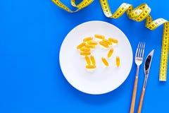 Pilules ou supplément diététique pour la perte de poids Traitement de l'obésité Traitement d'anorexie Pilules d'or de plat près photo stock