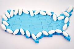 Pilules pharmaceutiques blanches au-dessus de carte de fond de l'Amérique Images libres de droits