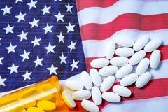 Pilules pharmaceutiques blanches débordant la bouteille de prescription au-dessus du drapeau américain Images libres de droits