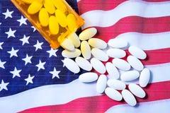 Pilules pharmaceutiques blanches débordant la bouteille de prescription au-dessus du drapeau américain photographie stock libre de droits