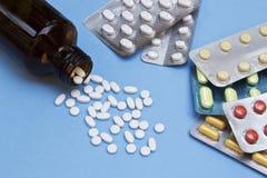 Pilules renversées hors de la bouteille de pilule avec les comprimés médicinaux sur le fond bleu image libre de droits