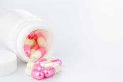 Pilules roses et jaunes de perle une bouteille de pilule sur le fond blanc Image libre de droits