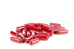 Pilules rouges (capsules) à l'arrière-plan blanc Photo libre de droits