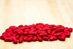 Pilules rouges de comprimés dragéifiés de sucre de rein sur la table en bois avec le PS de copie Photographie stock libre de droits