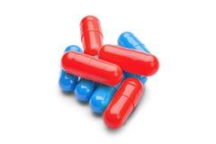 Pilules rouges et bleues de médecine sur un fond blanc d'isolement Image libre de droits