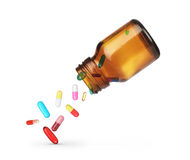 Pilules tombant d'un pot sur un fond blanc Photos stock