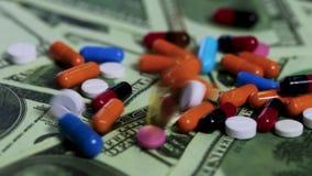 Pilules tombant sur des billets de banque du dollar, médicament cher, affaires pharmaceutiques banque de vidéos