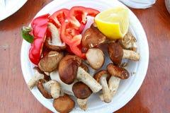 Pilz, roter Pfeffer und Zitrone auf der weißen Platte Lizenzfreie Stockfotos