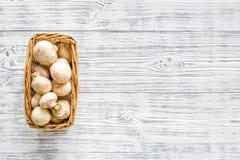 Pilzchampignons Frische rohe ganze Champignons im Korb auf grauem hölzernem Draufsicht-Kopienraum des Hintergrundes lizenzfreie stockfotos