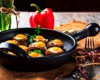Pilze angefüllt mit Wachtelei auf schwarzer Wanne Lizenzfreie Stockfotos