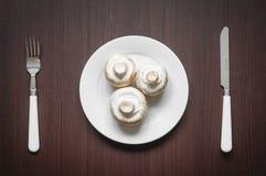 Pilze in der weißen Schüssel mit Messer und Gabel Ansicht von oben Lizenzfreie Stockbilder