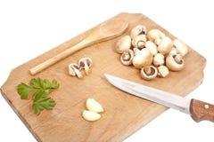 Pilze, Petersilie und Knoblauch auf einem hölzernen Vorstand Stockfotografie