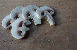 Pilze in Scheiben, Champignons auf einem Braun des hölzernen Brettes stockbild