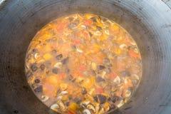 Pilzsuppe gekocht in einem großen Topf und mit dem Geruch eines Feuers stockfotos
