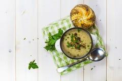 Pilzsuppe mit einem Brötchen und einer Petersilie Stockfotos