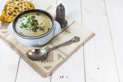 Pilzsuppe mit einem Brötchen und einer Petersilie Stockbild