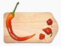 Pimentões, pimenta vermelha na placa de madeira Imagem de Stock