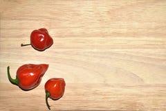 Pimentões, pimenta vermelha na placa de madeira Foto de Stock