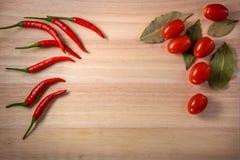 Pimentões Tomates e folha de louro na placa de madeira feita do bambu Imagem de Stock