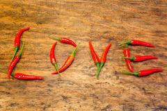 Piment comme lettres pour l'amour sur la table en bois Photo stock