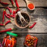 Piment conservé dans des pots en verre sur la table en bois Photographie stock