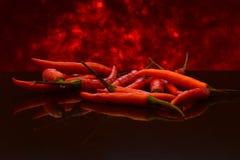 Piment ou poivrons de Cayenne rouges sur des flammes Images libres de droits