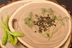Pimenta da Jamaica, aneto e salada no corte de madeira Fotos de Stock
