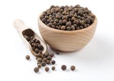 Pimenta da Jamaica na bacia de madeira e na colher isoladas no fundo branco Especiarias e ingredientes de alimento imagens de stock