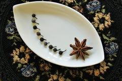 Pimenta de Java e anis de estrela em uma placa decorativa foto de stock