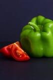 A pimenta de sino verde, o ano do capsicum, e o tomate vermelho remendam contra uma obscuridade - fundo azul com espaço da cópia Fotografia de Stock Royalty Free