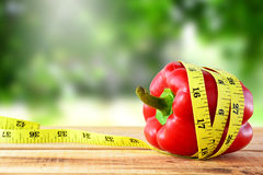 Pimenta de sino vermelha com a fita de medição amarela, conceito da dieta Imagens de Stock