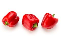 Pimenta de sino vermelha com metade e folhas isoladas no branco Imagens de Stock