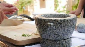 Pimenta e umas outras especiarias no almofariz de pedra com o pilão para o molho de pimentão tailandês Mulher que prepara o molho filme