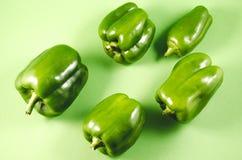 Pimenta verde da paprika isolada em um fundo verde /Heap do pimento verde fresco da paprika no fundo verde Vista superior fotografia de stock royalty free