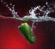 Pimenta verde que cai na água Fotos de Stock Royalty Free