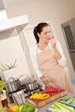 Pimenta vermelha cortante da mulher feliz na cozinha Foto de Stock Royalty Free