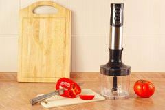 Pimenta vermelha desbastada com tomate e um misturador na mesa de cozinha Foto de Stock Royalty Free