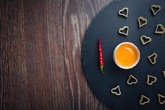 Pimenta vermelha do ovo quebrado em um fundo preto foto de stock