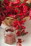 A pimenta vermelha picante moeu no frasco de vidro, com pimentas secadas saudáveis na cesta Imagem de Stock Royalty Free