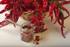 A pimenta vermelha picante moeu no frasco de vidro, com pimentas secadas saudáveis na cesta Fotos de Stock