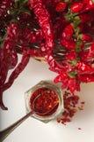A pimenta vermelha picante moeu no frasco de vidro, com pimentas secadas saudáveis na cesta Fotografia de Stock