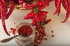 A pimenta vermelha picante moeu no frasco de vidro, com pimentas secadas saudáveis na cesta Imagem de Stock