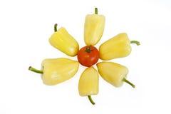Pimentas amarelas que encontram-se no fundo branco No meio é um tomate vermelho Foto de Stock Royalty Free