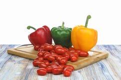 Pimentas de Bell e tomates do bebê em um fundo do branco da placa de desbastamento fotografia de stock