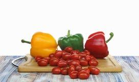 Pimentas de Bell e tomates do bebê em um fundo do branco da placa de desbastamento fotos de stock royalty free