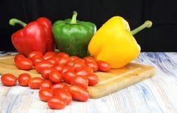 Pimentas de Bell e tomates do bebê em um fundo preto da placa de desbastamento fotos de stock royalty free