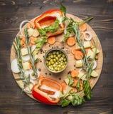 Pimentas de Bell, ervilhas enlatadas, cenouras cortadas, batatas e ervas em um vegetariano rústico de madeira c da opinião superi Foto de Stock Royalty Free