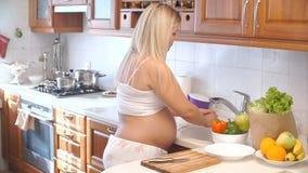 Pimentas de lavagem da mulher gravida na cozinha Vegetais para a salada video estoque