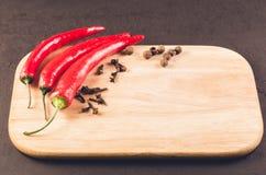 Pimentas de pimentão encarnados e pimentas e especiarias de pimentão encarnados das especiarias em uma placa de corte vazia Copie fotos de stock royalty free