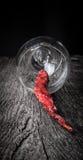 Pimentas de pimentão encarnados em um vidro em um fundo de madeira escuro Imagens de Stock Royalty Free